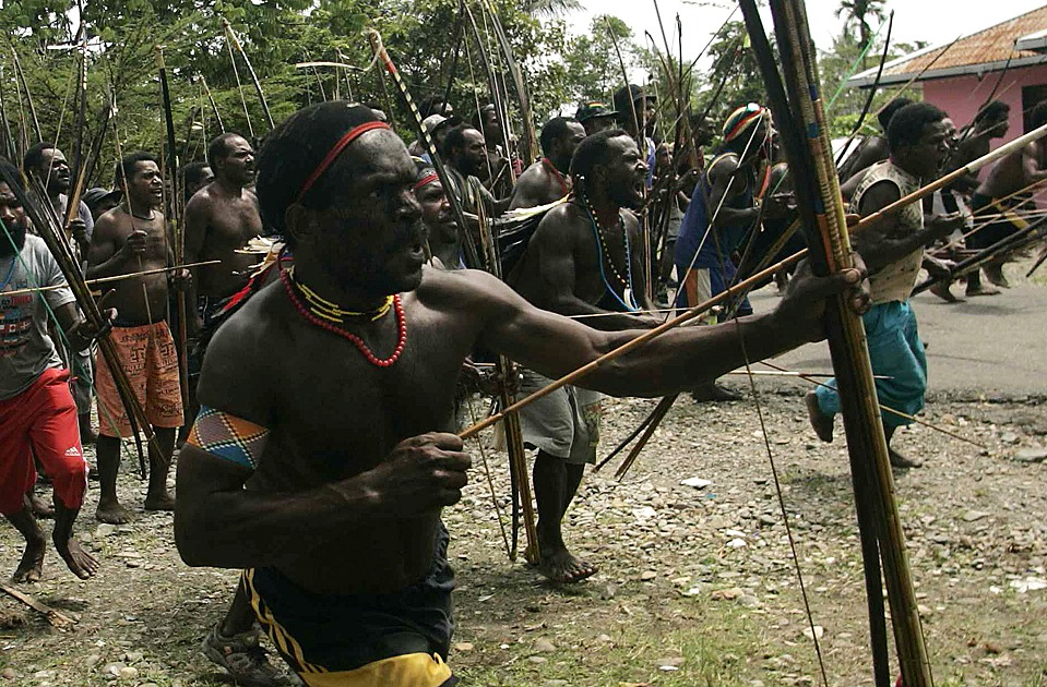 Dani tribesmen hold their weapons as they attack the Damal tribe during intertribal wars in the village of Old Kwaki in Timika